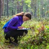 The picture shows a student in the forest, squatting and taking notes on a paper.