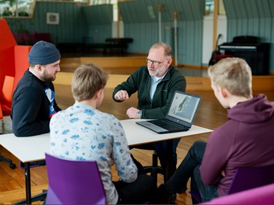 Picture of Dag Fjeld in a conversation with some students.