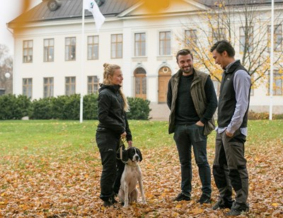 Three  students  with a dog outside a building in Skinnskatteberg, photo.