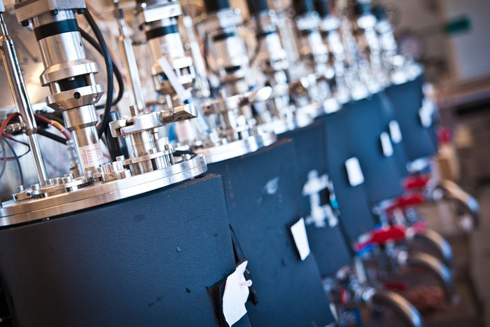 Blue, cylindrical machines in a row indoors, photo.