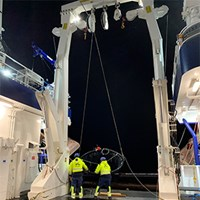 A trawl for fish larvae is set from the aft deck of the research vessel Svea in the middle of the night by two seamen. Photo.