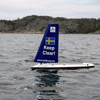 SLU Aqua Sailor in the water. It looks like a windsurfing board. On its sail is the SLU logo, a swedish flag and  the text Keep clear and www.sailbuoy.no.