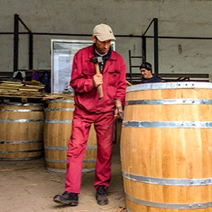 A man dressed in red is holding a hammer close to a large wine barrel, photo.