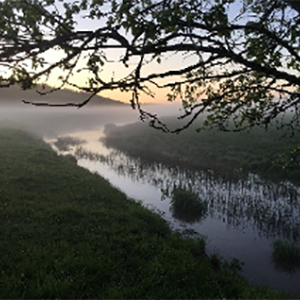 A river at sunrise with fog over. Photo.