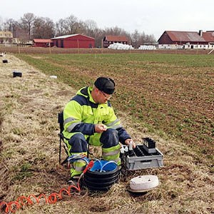 A man with measuring instruments on a field, photo.