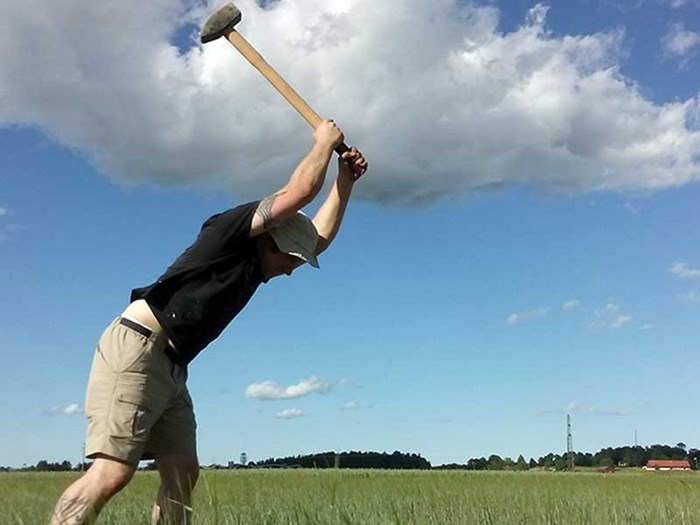 A man swings a hoe against a blue sky, photo.