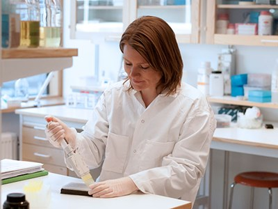 Woman pipetting in a lab, photo.