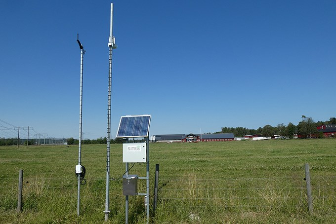 A mast with a camera by a field. Photo.