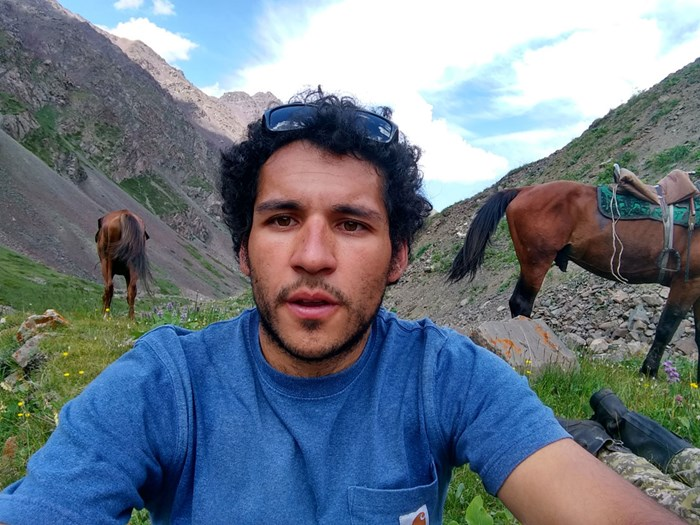 Raul in mountain, horses in the background. Photo.