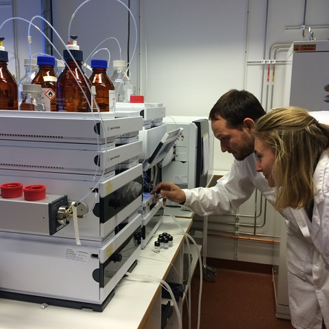 Two chemists inspecting an analysis instrument