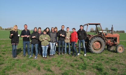 Twelve persons in front of a tractor. Photo.