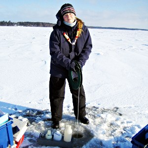 Woman standing on an ice covered lake taking samples from a drilled hole. Photo.