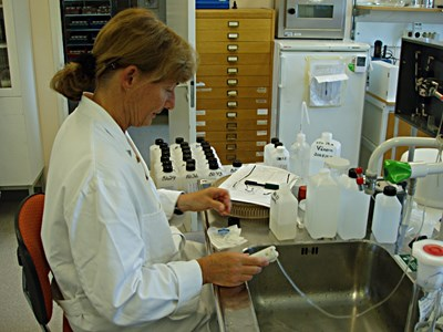 A person wearing a labcoat, performing analeses, photo.