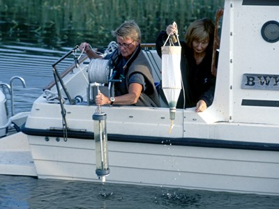 Two persons collecting samples from a boat, photo.