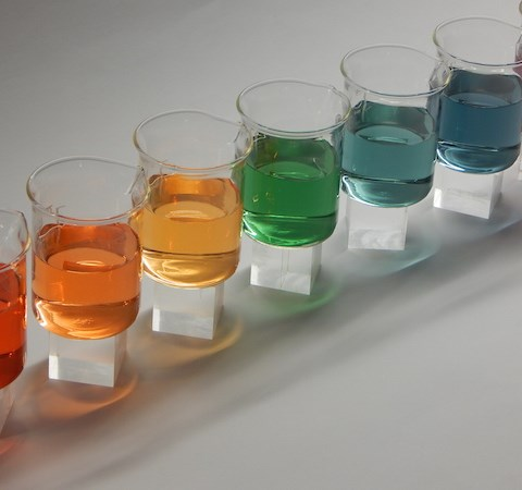 Beakers filled with liquids in different colours, photo.