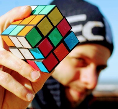 A man holds up a rubics cube, outside.