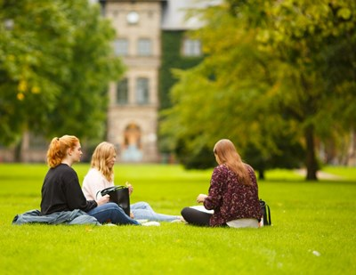 Three female students sit on the lawn in Alnarsparken, photo.