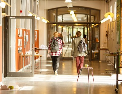 Two female students walking in a corridor, photo.